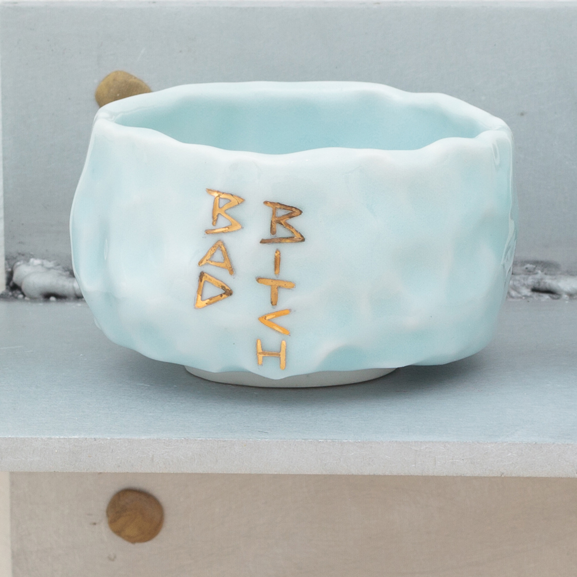 "<p><span class=""name"">Patrice Renee Washington</span><br><em>Bad Bitch Cup (3)</em><span class='media'>Glazed porcelain, gold luster, aluminum, Sculpey clay</span>2.1625 x 2.75 x 2.75 in  (5.5 x 7 x 7 cm)<br>2016<br><a class='inquire' href='mailto:info@gildargallery.com?subject=Artwork Inquiry PWAS0004&body=I am interested in finding out more about Bad Bitch Cup (3) by Patrice Renee Washington'>Inquire</a></p>"